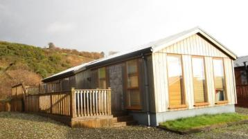 WATCH: This affordable shoreside log cabin is a refreshing spin on the usual holiday park home